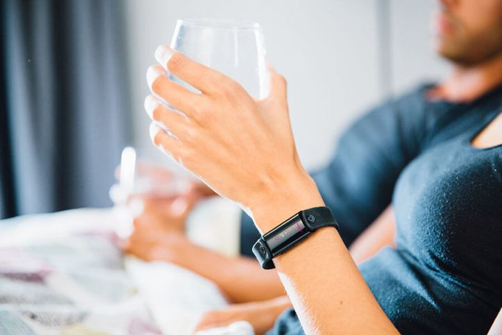 Person wearing LVL wristband while holding glass of water