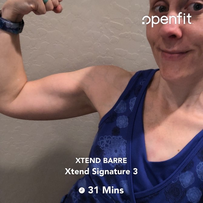 Flexing after doing an Xtend Barre workout in the OpenFit app.