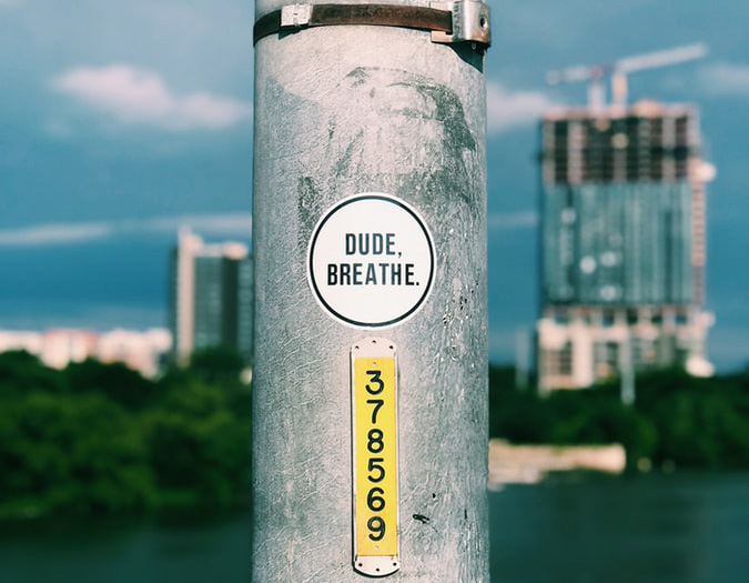 Dude, Breathe - A sticker on a city pole.